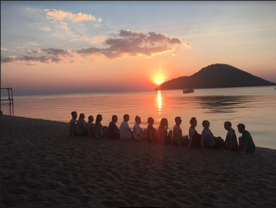 A group of students at Lake Malawi during sunset.